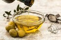olive oil being poured into a glass container with olives around the container on a table