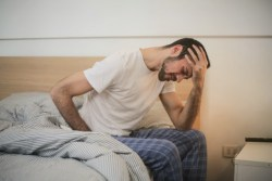 Guy with stomach pain sitting at the edge of his bed