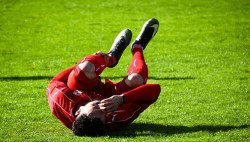 Athlete on the field in pain due to leg cramps
