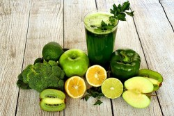 glass of green juice surrounded by all the green fruits and vegetables used to make it.