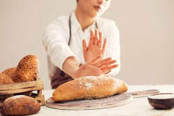 digestive problems with bread: woman pushing away a loaf of bread