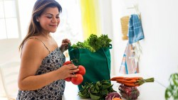 woman with grocery bag filled with macrobiotic diet foods