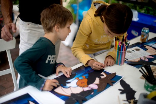 Photo of two children creating paper bats