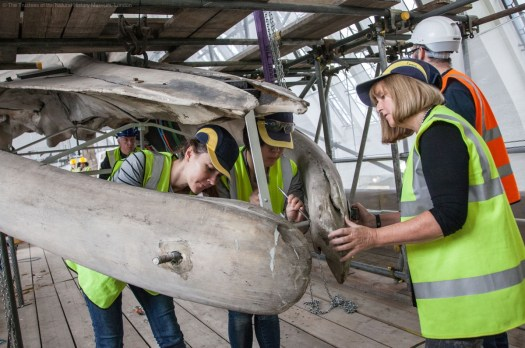 Photo showing conservators chipping away the plaster around the bolt