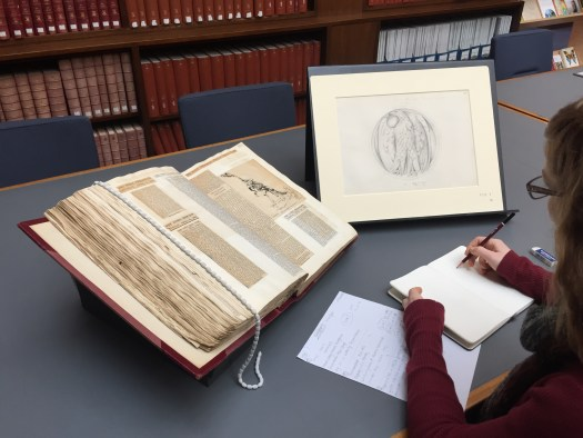 Photo showing a large book of press cuttings on a table, with a Waterhouse sketch on a stand and Zoe taking notes and drawing in her sketchbook