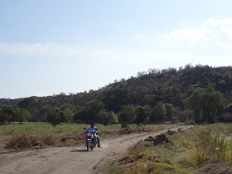 Photo showing a dirt road with motorcyclist and passenger coming towards the camera, and wooded hillside in the background