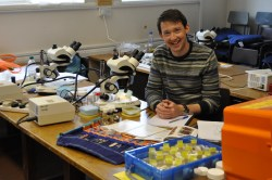 Photo showing Anthony sat at a desk with an array of specimens, books and a microscope in front of him