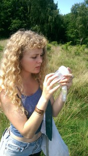 Photo showing Katy staring at a specimen jar she's holding in a field.