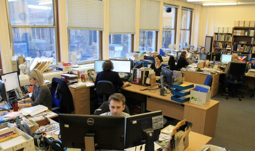 Photograph showing the Library and Archives staff at their desks working in their office