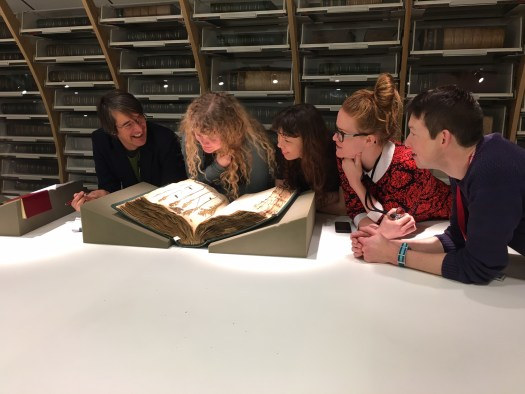 Photo showing the trainees looking at an historic volume of herbarium sheets in the collection