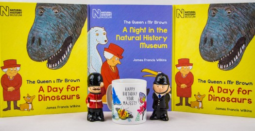 a display of books featuring the Queen as a calendar with toys and a mug placed in front