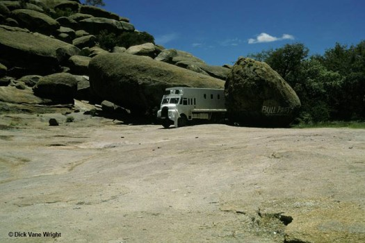 Colour archival photograph showing a white truck in the background parked between some very large, oval boulders with a flat ridge stretching out in front of it.
