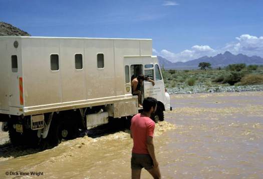 Colour archival photograph showing the truck driving through muddy water from a flash flood with a man walking beside it