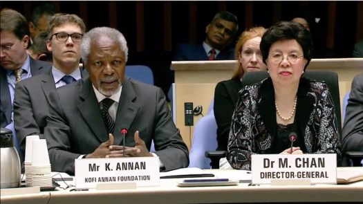Photo showing Kofi Annan (left) and Dr Margaret Chan (right) seated at a table, with aides and other delegates seated in the background behind them.
