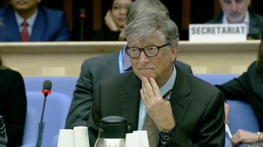 Photo of Bill Gates seated, looking slightly to his right and with his hand to his chin. Aides and other delegates are partially visible seated in the background.