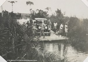 Black and white archival photograph showing the Chrysler on a raft being manoeuvred along a narrow river between reeds by 10 men with the owner posing in front, looking backwards