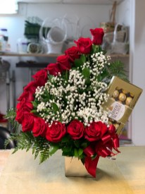 LVRE023- A row of red roses with baby breath and a box of chocolates.Special: $135.00