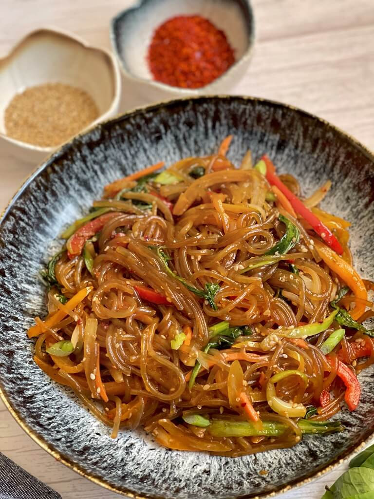 Vegetarian Japchae - these stir-fried Korean glass noodles (sweet potato noodles) are the perfect combination of sweet, salty, and nutty. With a glossy sesame oils sheen and crunchy veggies, it's quick to whip up as a weeknight dinner!