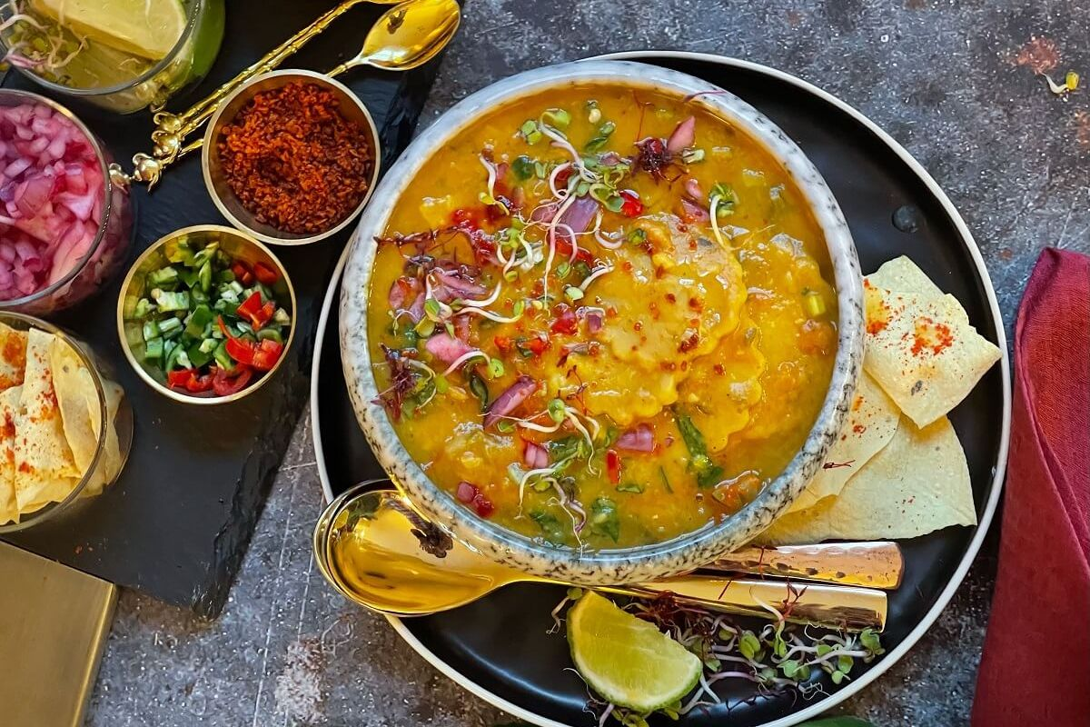 Dal Dhokli - this hearty, one-pot meal features melt-in-your-mouth wheat dumplings simmered in a comforting dal. Packed with veggies and spiced up with crunchy toppings, this velvety dish is a nutritious weeknight dinner!