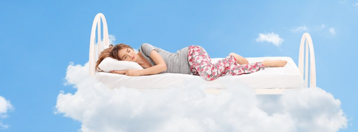 A woman sleeping in a bed, surrounded by white clouds.