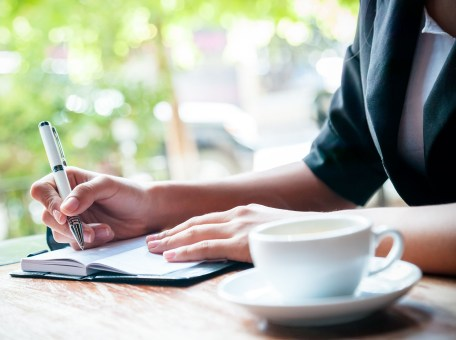A woman writing in a journal while sitting next to a window and enjoying a cup of coffee.