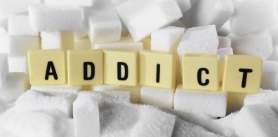 Sugar cubes support tiles that spell out the word addict.