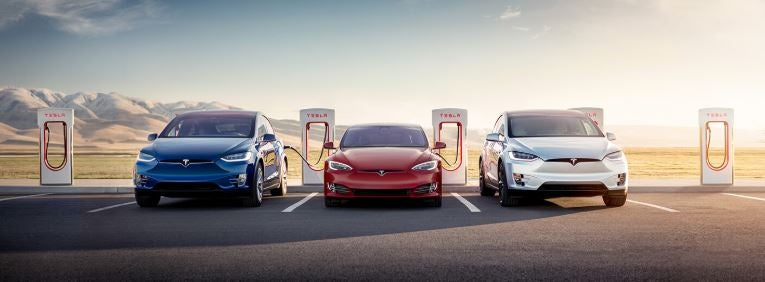 Tesla model 3, Tesla model S, and Tesla model X being supercharged in front of a mountainous landscape