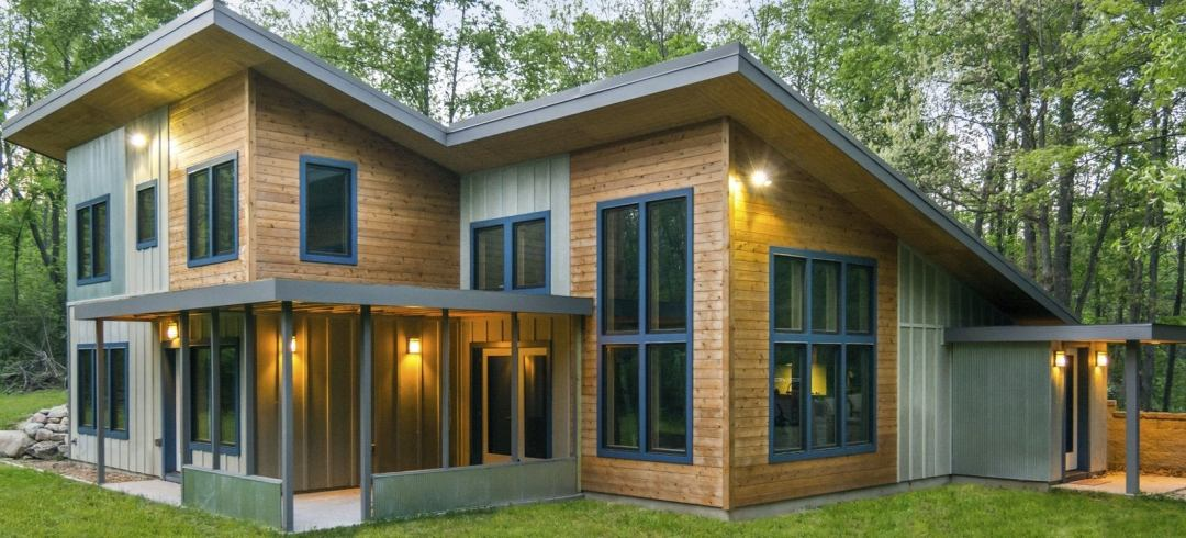 A passive solar home with windows on every wall, wood paneling and diagonal roofs sits surrounded by trees.