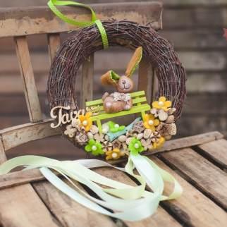 Padon ülő nyúl tavaszi színpompában, nyírfaágas alapon