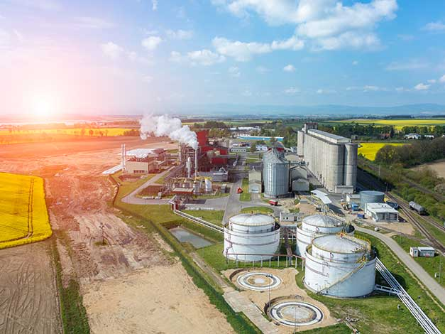 The sun peaks over the modern biofuel factory surrounded by lush grass.