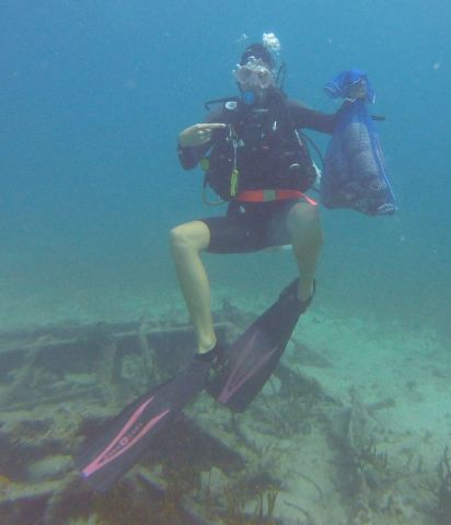 diver with trash bag under water