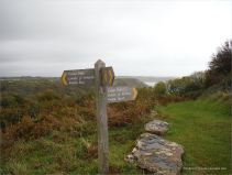 Sign post on top of the headland directing to Pwll Du Bay