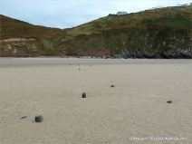 View looking towards Rhossili village on the cliff top, with stumps of wooden posts belonging to an unidentified structure on Rhossili beach
