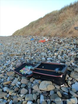 Flotsam suitcase on beach pebbles