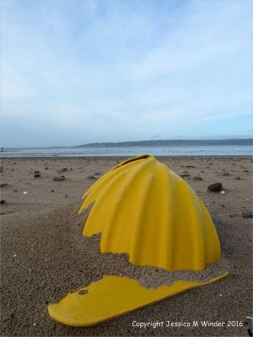Yellow plastic hard hat washed ashore as flotsam