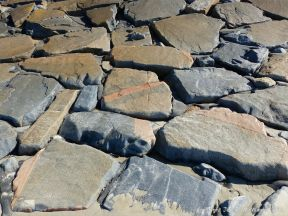Stone slabs at the base of the sea wall at Rocquaine bay