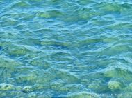 Texture and pattern of blue sea water over a yellow sandy shore
