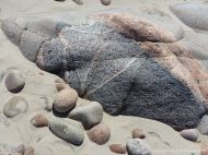 Rock outcrop in the sand at Black Brook Cove