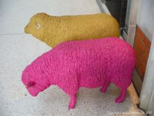Two life-sized models of sheep at a railway station