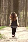 A little girl walking in the woods
