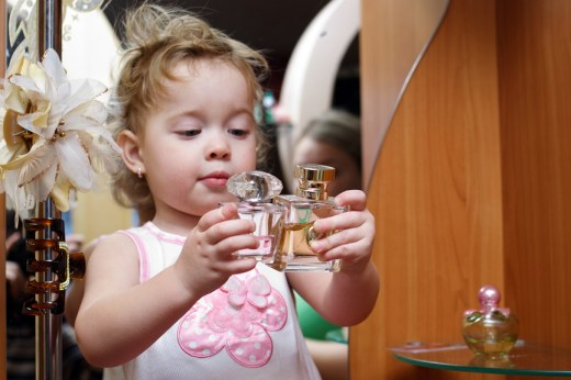 child with perfume bottles