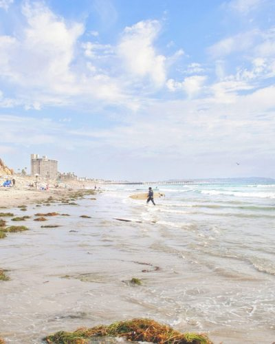 walking on the beach with surfers and kelp in pacific beach, ca