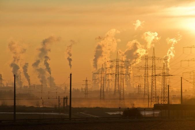 Vor einem abendlichen Himmel sind Schornsteine und Strommasten zu sehen. Die Schornsteine emittieren große Mengen an klimaschädlichem CO2.