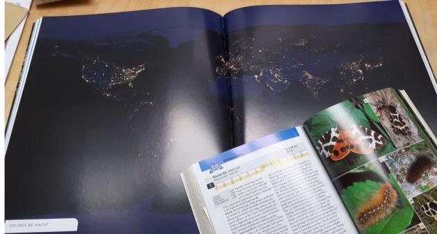 """Im Hintergrund der """"Atlas unserer Zeit"""" von Alastair Bonnett (darüber kommt bald noch ein eigener Blogeintrag), die Lichtpunkte weisen auf große menschliche Siedlungn hin. Im Vordergrund der """"Kosmos-Schmetterlingsführer""""."""
