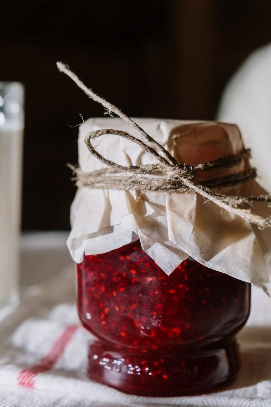 red and white glass jar with white ribbon