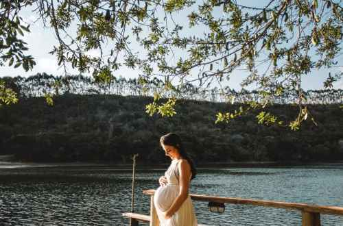 photo of pregnant woman standing on dock