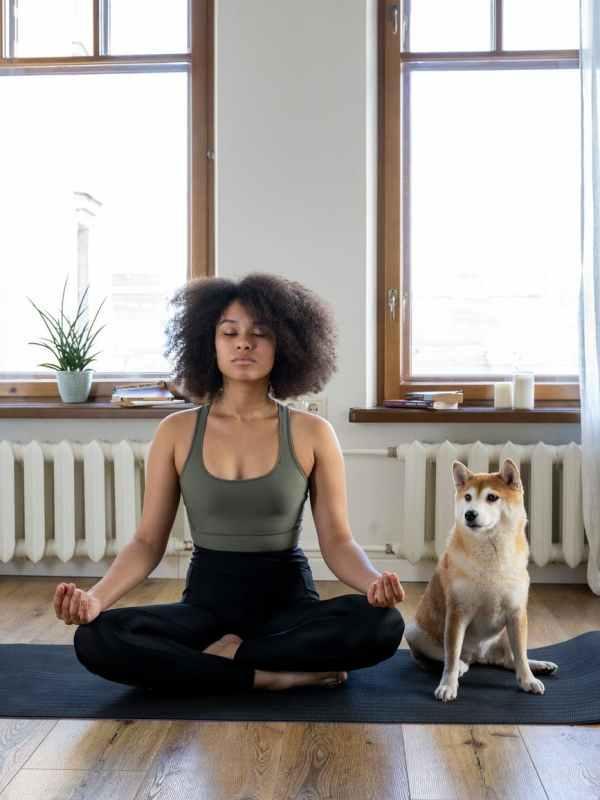 woman meditating beside her dog