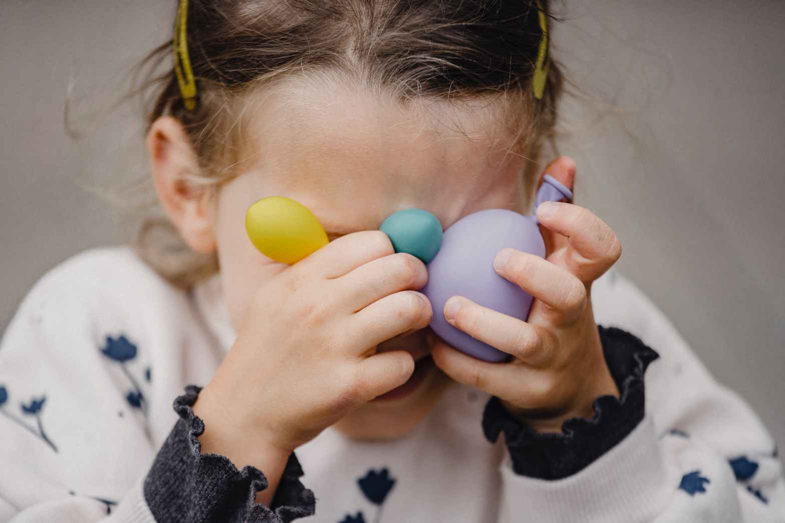 unrecognizable girl covering face with assorted balloons on street