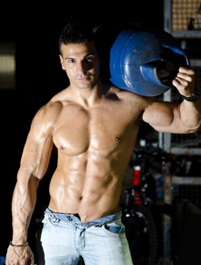 Muscular young man shirtless, carrying gas tank on shoulder