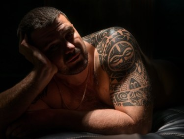 Handsome young man with a tattoo in a dark room